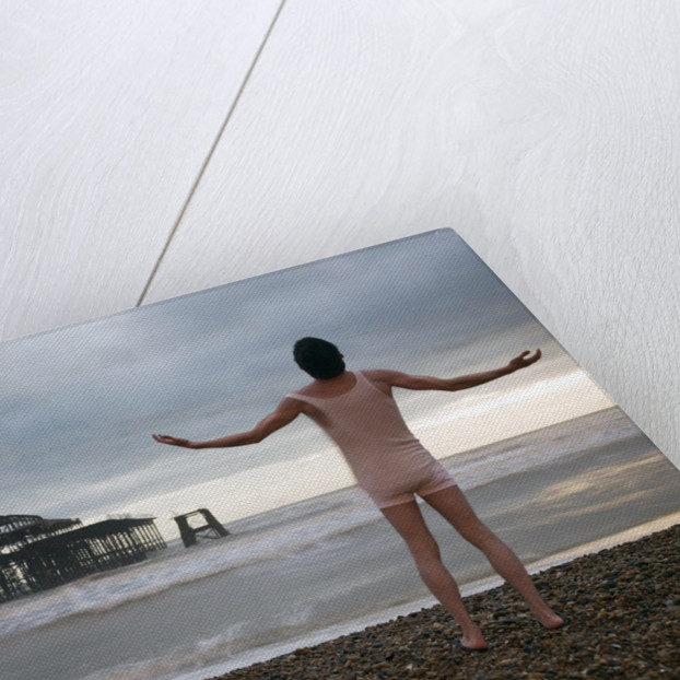 Man standing on beach with outstretched hands, rear view, Brighton by Assaf Frank