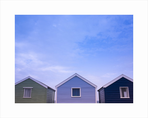 Beach huts in a row against sky by Assaf Frank