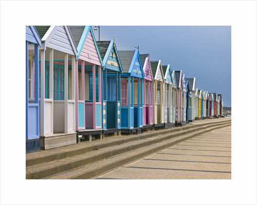 Multi coloured beach huts in a row by Assaf Frank
