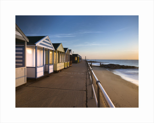 Beach huts in a row at sunrise by Assaf Frank