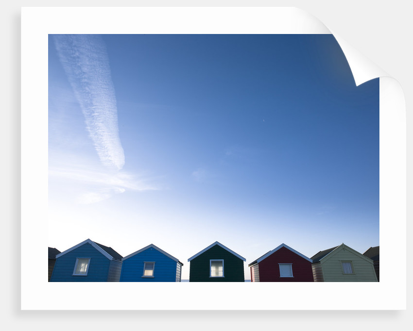 Beach huts in a row against blue skies by Assaf Frank