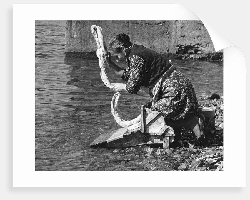 Woman washing clothes in a river, Portugal, 1973 by Tony Boxall