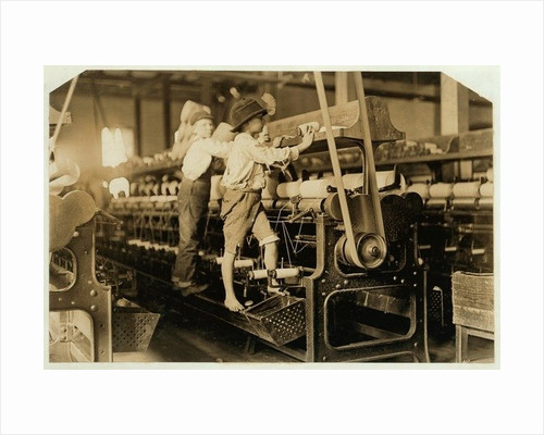 Small boys climbing on spinning frame to mend broken threads and replace empty bobbins at Bibb Mill, Macon, Georgia by Lewis Wickes Hine