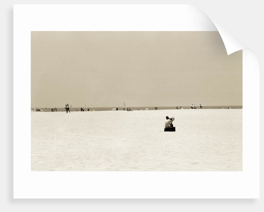 Man sitting on a beach playing his horn by Stephen Spiller