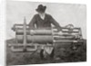 Hiram Maxim holding one of his flying machine engines by Anonymous