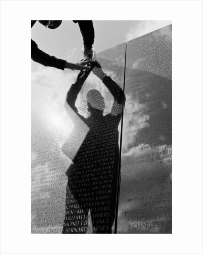 Reflection of a volunteer at the Vietnam Veterans Memorial by Michael Katakis