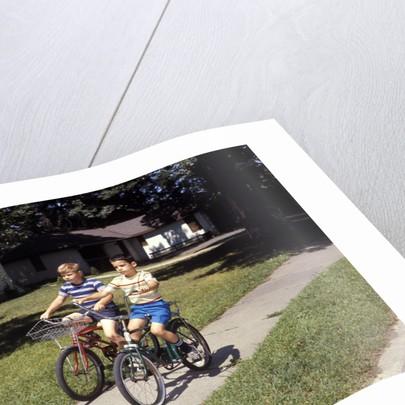 1970s Two Boys Riding Bikes Down Suburban Neighborhood Sidewalk by Corbis