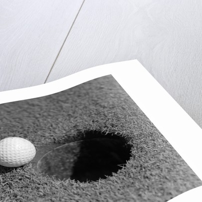 1950s Close-Up Of Golf Ball On Green On Very Edge Of Cup by Corbis