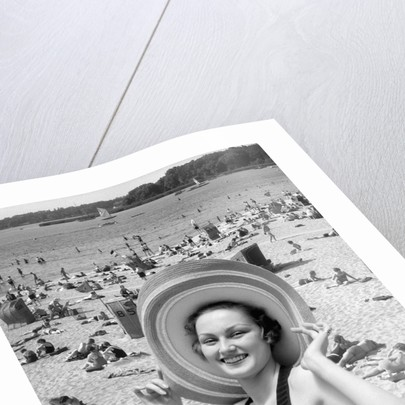 1930s Vacation Montage Portrait Woman In Bathing Suit Wearing Large Straw Hat And Scene Of Crowded Beach by Corbis