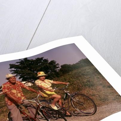 1970s Senior Elderly Retired Couple Riding Bikes Wearing Straw Hats Hawaiian Print Shirts by Corbis