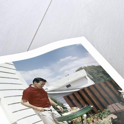 1960s Man Wearing Red Shirt Grilling Steak On Backyard Brick Patio by Corbis