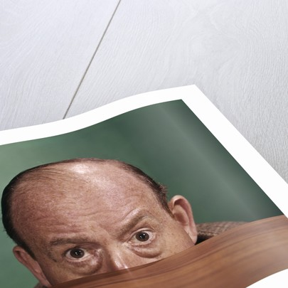 1960s Balding Man Peeking Over Desktop With Only Top Half Of Head Showing by Corbis
