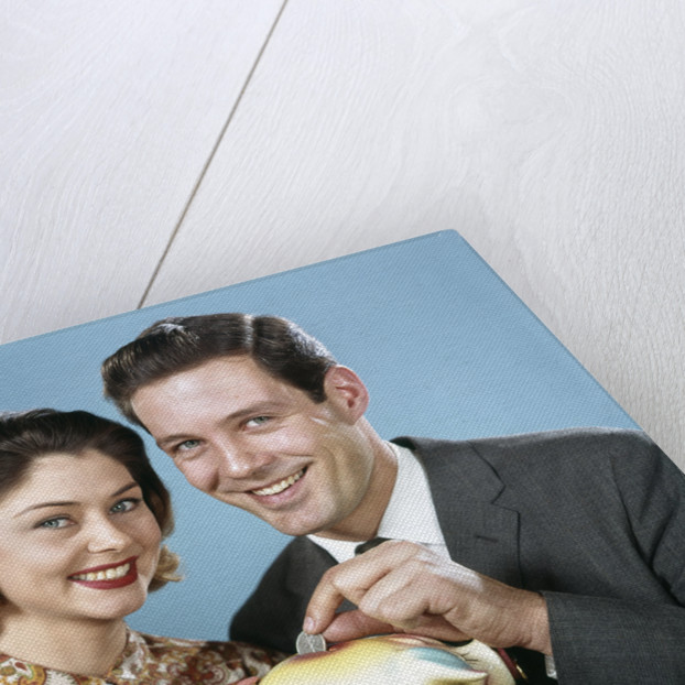 1950s 1960s Young Couple Man And Woman Put Quarter In Savings Piggy Bank by Corbis
