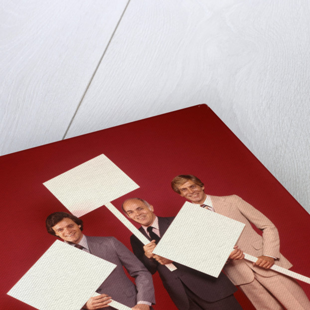 1970s Three Business Men Wearing Suits Each Carrying Blank Sign Placard Red Background by Corbis