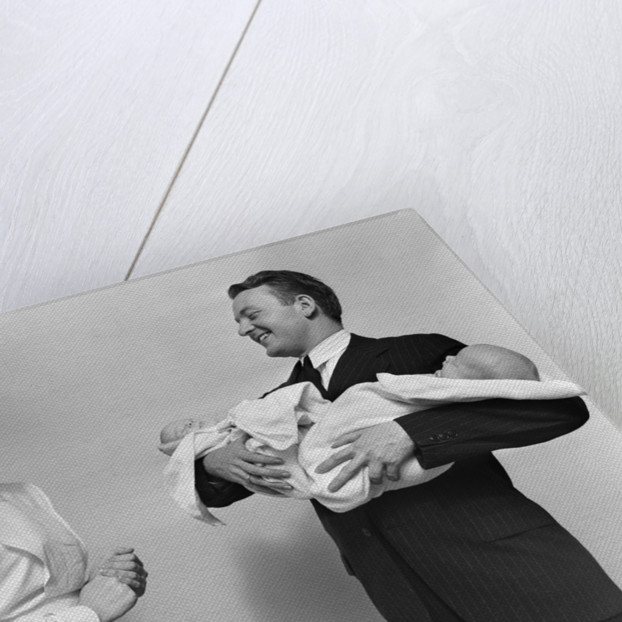 1930s 1940s Woman Nurse Talking With Man Proud New Father Holding Newborn Twin Babies by Corbis