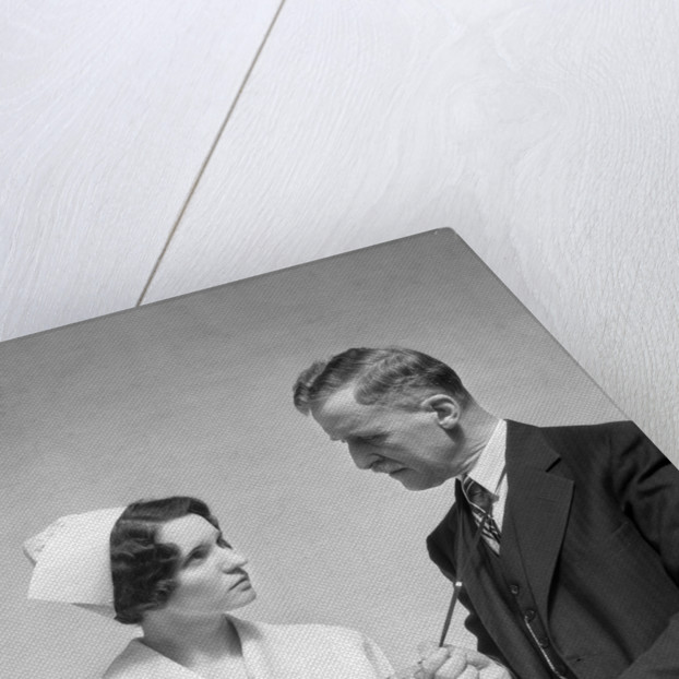 1930s Doctor In Suit And Necktie Confers With Nurse In Uniform And Cap Holding Clipboard Chart by Corbis