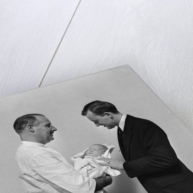 1930s 1940s Man Doctor Showing New Born Infant Baby To Proud Father by Corbis