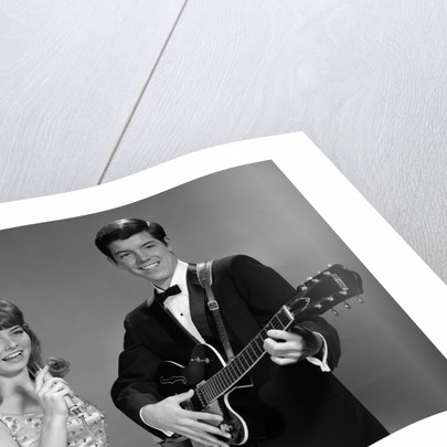 1960s Teenage Entertainment Duo Man Playing Guitar And Woman Singing Holding Microphone by Corbis