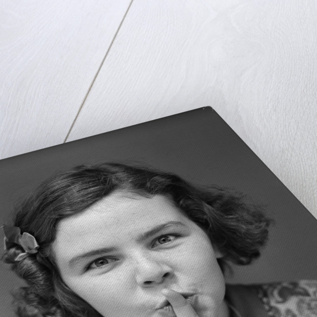 1930s Portrait Of Young Girl With Finger To Mouth Making Shush Be Quiet Expression by Corbis