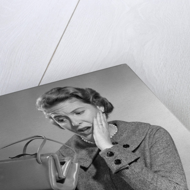 1950s Woman With Exaggerated Expression Hand On Face Looking Inside Her Purse by Corbis