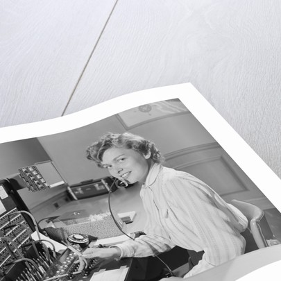 Smiling woman office telephone switchboard operator by Corbis