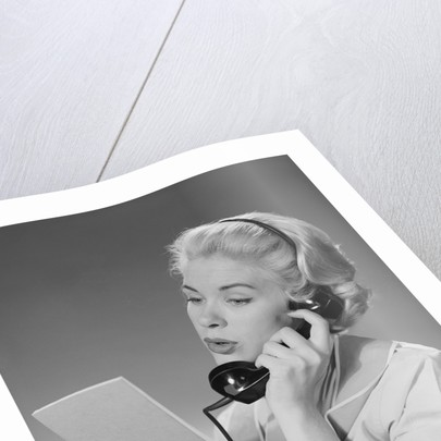 Blond woman talking on telephone reading list by Corbis