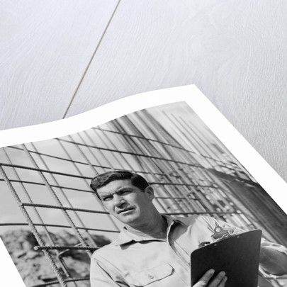 Man on construction site holding clipboard by Corbis