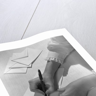 Woman's hands holding pen writing letter on stationery by Corbis