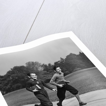 Two smiling boys running carrying school books by Corbis