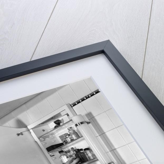 1940s woman reaching into bathroom medicine cabinet by Corbis