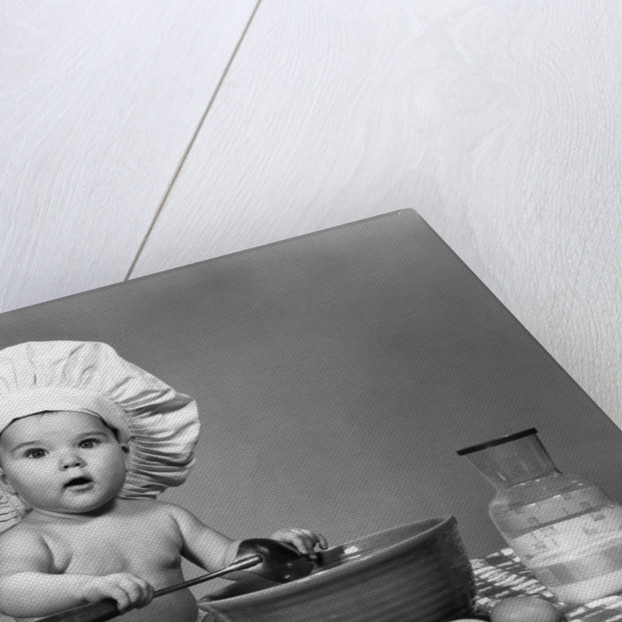 1960s baby seated on checkered tablecloth wearing chef's hat mixing eggs milk & flour in large bowl looking at camera by Corbis