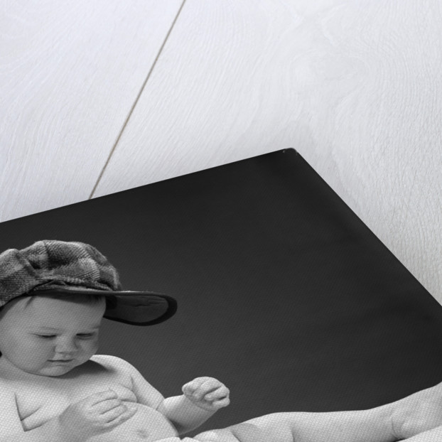 c06da2184 1960s baby in diaper wearing sherlock holmes deerstalker style  double-billed cap with magnifying glass resting on leg inspecting a clue