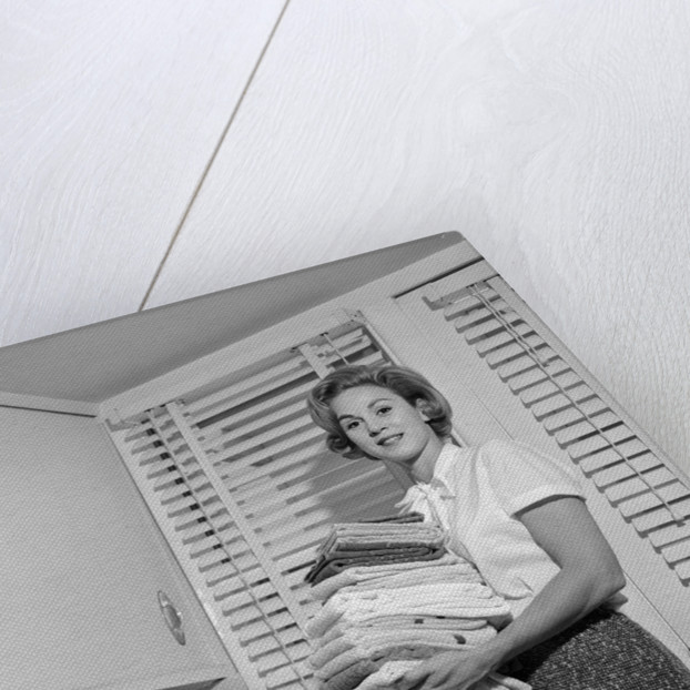 1960s woman holding folded laundry looking at camera by Corbis