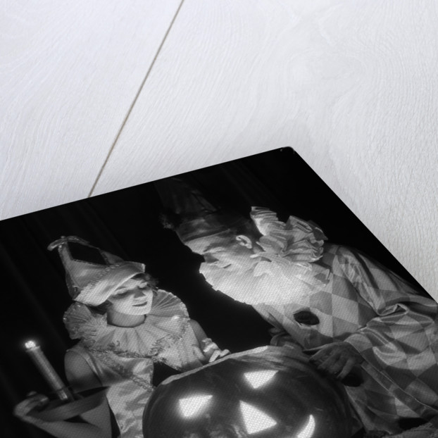 1920s 1930s couple in costumes looking down into candle light from carved pumpkin jack-o-lantern by Corbis