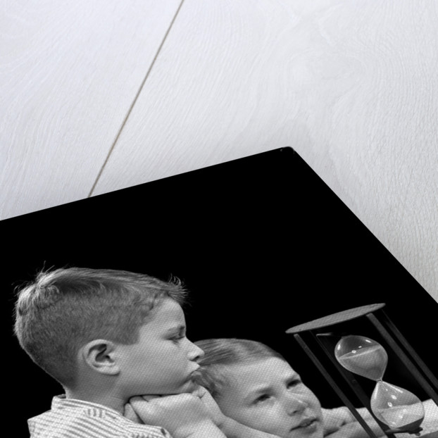 1940s two boys waiting watching sand falling in hourglass by Corbis