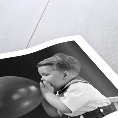 1940s boy blowing up balloon by Corbis