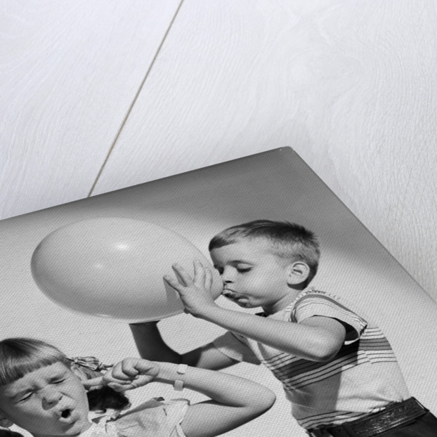 1950s little boy blowing up big balloon little girl with fingers in ears eyes closed by Corbis
