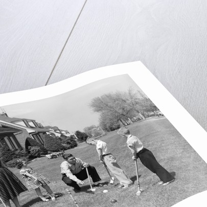 1950s family mother father 3 children playing croquet front lawn suburban home by Corbis
