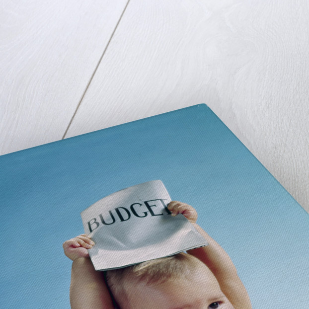 1960s baby holding budget sign above his head by Corbis