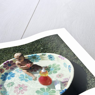 1970s baby sitting in plastic backyard kiddy pool viewed from above by Corbis