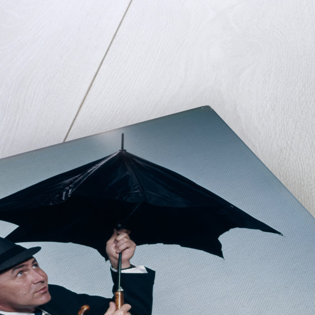 1960s businessman wearing hat opening umbrella to protect from rain by Corbis
