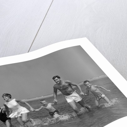 1960s Family Holding Hands Running Together In Water At Seashore by Corbis