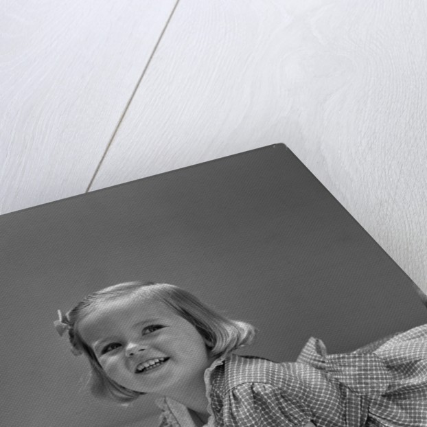 1940s Little Blond Girl Lying On Floor Looking Up And Aside Smiling From Reading A Picture Book by Corbis