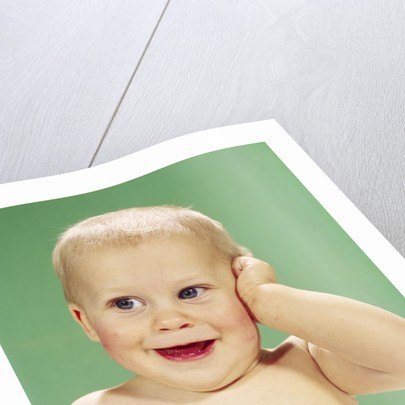 1960s Smiling Happy Baby Looking Off To The Side With Hand Touching Face by Corbis