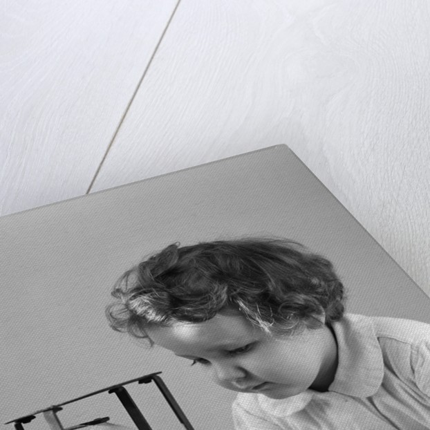 1940s young girl leaning on table staring at hourglass by Corbis