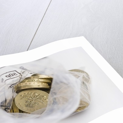 Looking down into an open money bag of pound coins by Corbis