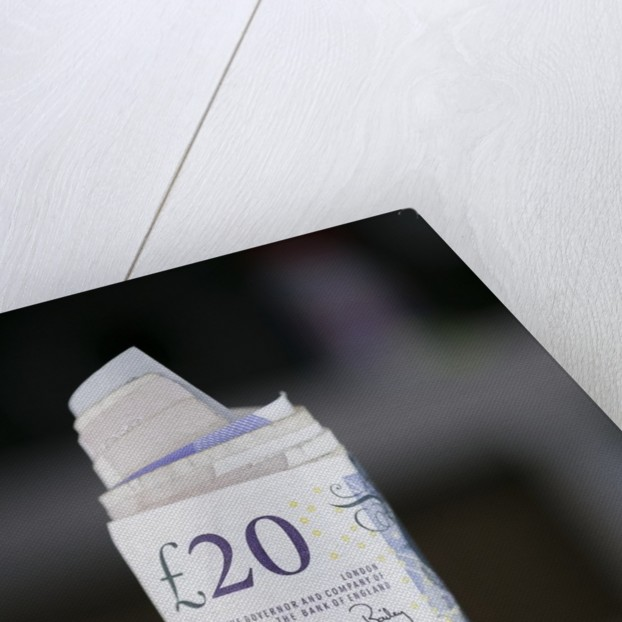 A roll of twenty pound notes on a table by Corbis