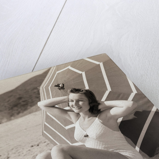 Sunbather Leaning Against Umbrella by Corbis