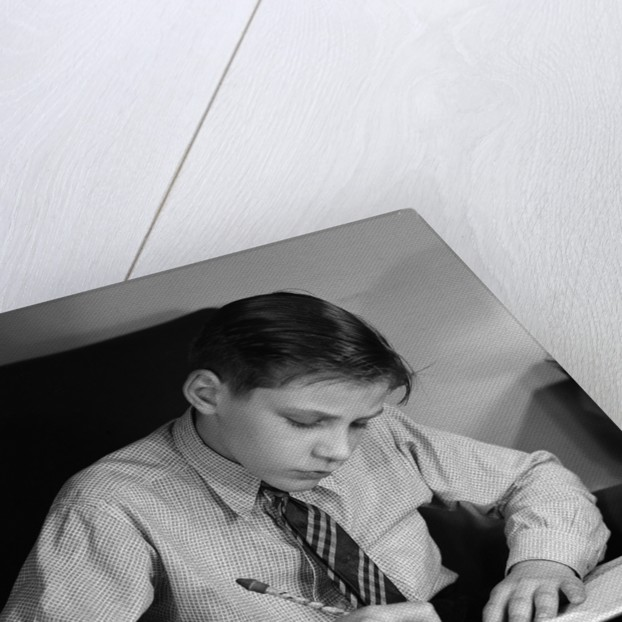 Seated Boy Doing Homework by Corbis