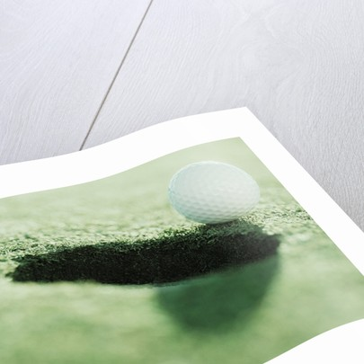 Golf Ball on the Edge of the Hole by Corbis
